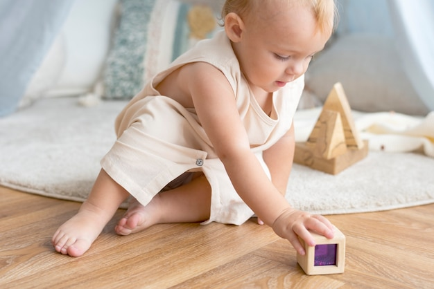 Dziewczynka bawi się drewnianym klockiem