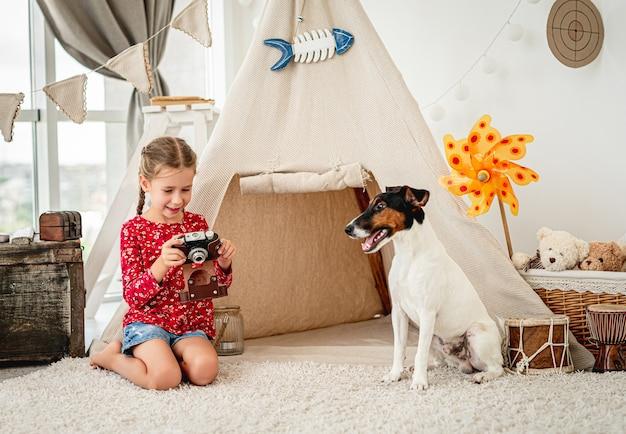Dziewczynka bawi się kamerą filmową obok psa foksterier w sali zabaw