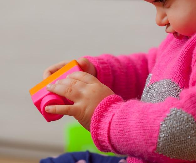 Dziewczynka bawi się klockami z miękkiej gumy
