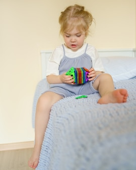 Dziewczynka bawi się magnetyczną zabawką konstrukcyjną siedząc na łóżku