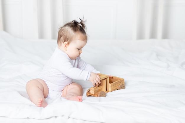 Dziewczynka bawi się maszyną do pisania drewniane zabawki na łóżku w domu, pojęcie zabawy i rozwoju dzieci