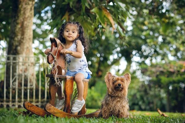 Dziewczynka bawi się na bardzo szczęśliwym drewnianym koniu obok swojego psa yorkshire. znajdują się w naturalnej przestrzeni zewnętrznej