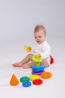 Dziewczynka bawi się piramidą kolorowe zabawki, siedząc na podłodze