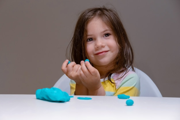 Dziewczynka bawi się plastiliną (grać ciasto) na szarym tle.