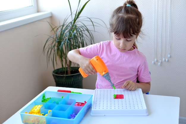 Dziewczynka bawi się w dziecięcą edukacyjną układankę konstruktora za pomocą śrubokręta, śrubokręta i shuruki z wielokolorowymi geometrycznymi kształtami. koncepcja kreatywnego rozwoju przedszkolaka.
