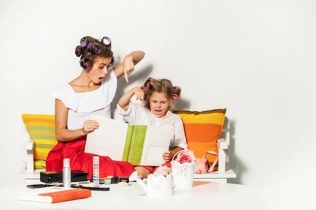 Dziewczynka bawi się z matką i patrząc na album fotograficzny na białym tle