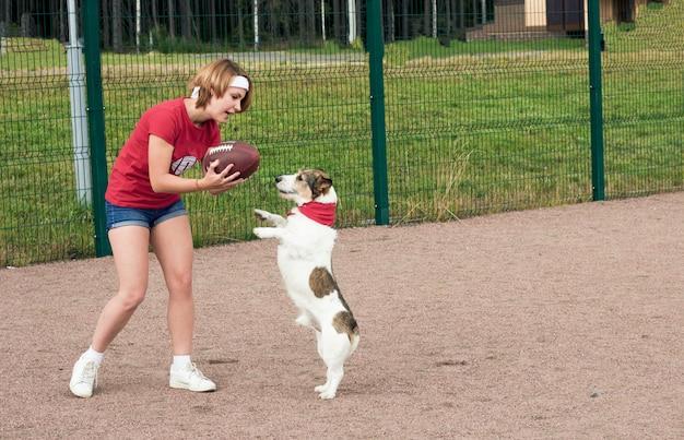Dziewczynka bawi się z psem w futbol amerykański.