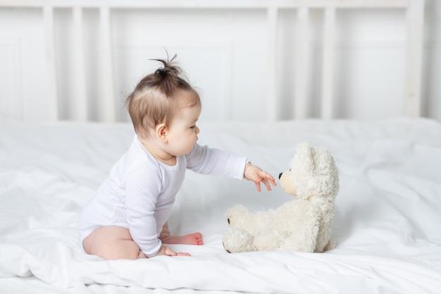 Dziewczynka bawi się zabawką misia na łóżku w domu, pojęcie zabawy i rozwoju dzieci