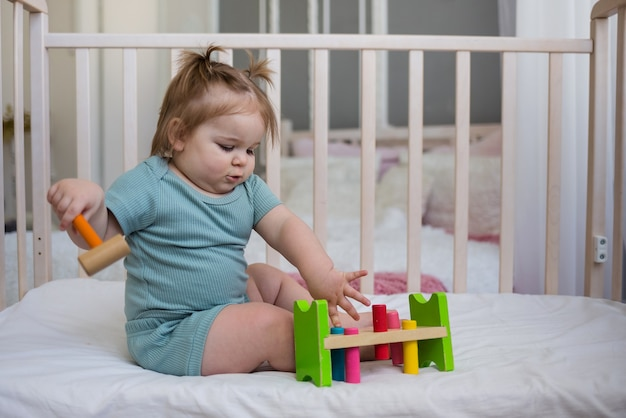 Dziewczynka bawi się zabawkami edukacyjnymi w łóżeczku dziecięcym w sypialni