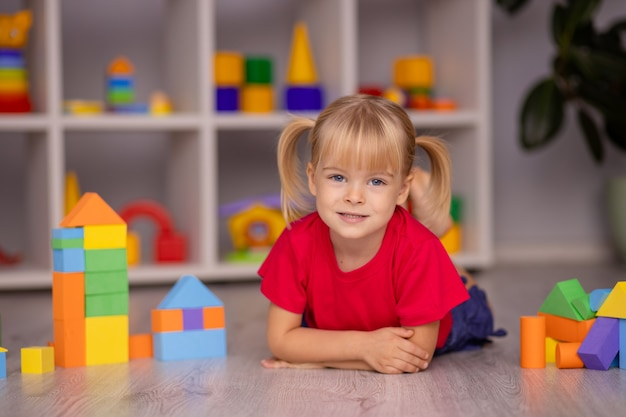 Dziewczynka bawi się zabawkami w domu, przedszkolu czy żłobku. rozwój dziecka.