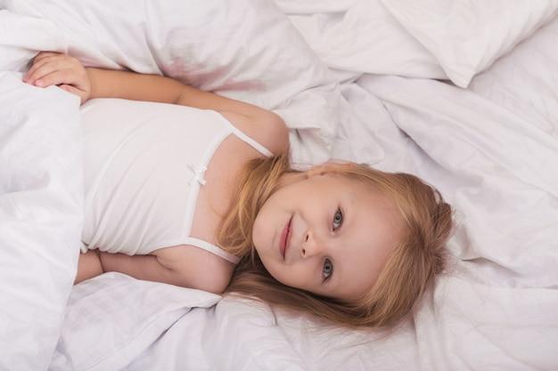 Dziewczynka bawić się w piżamie na łóżku