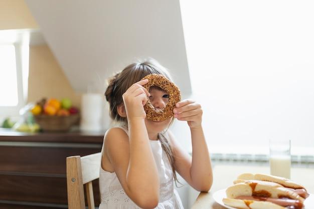 Dziewczynka bawić się z preclem z ziarnami