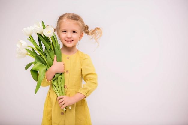Dziewczynka blondynka z bukietem tulipanów na jasnym tle