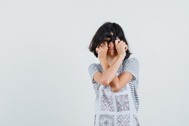 Dziewczynka chowająca oczy za włosami w koszulce, fartuchu,