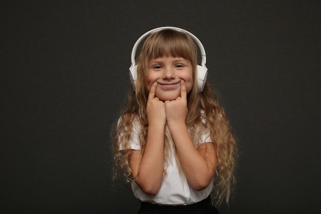 Dziewczynka cieszy się muzyką w jej dużych białych słuchawkach i uśmiechem.