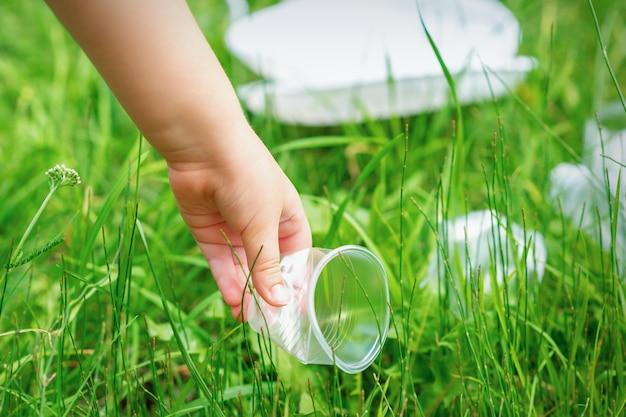 Dziewczynka czyści plastikowe naczynia na zielonej trawie w parku