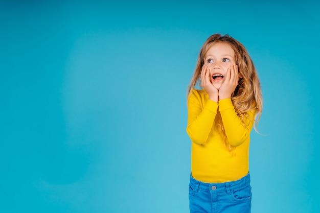 Dziewczynka dziecko amased i odwracając na białym tle na niebieskim tle.