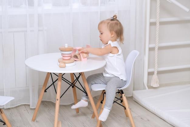Dziewczynka dziecko bawi się drewnianymi zabawkami przy stole. mała śliczna dziewczyna z naturalnymi zabawkami.