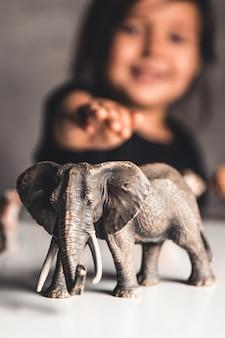 Dziewczynka dziecko bawi się zabawkami zwierząt przy stole
