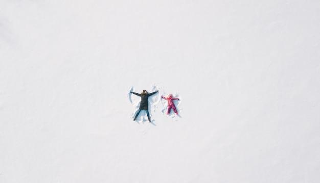 Dziewczynka dziecko i matka, grając i robiąc anioła śniegu w śniegu. płaski widok z góry