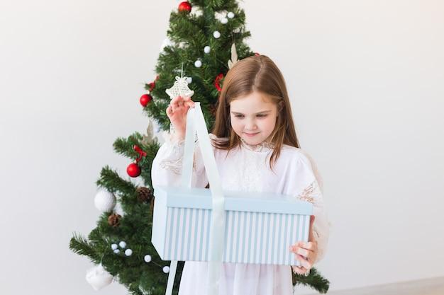 Dziewczynka dziecko otwiera pudełko obok choinki