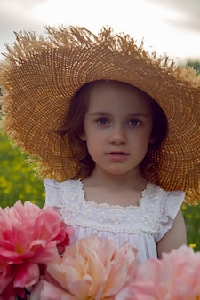 Dziewczynka dziecko w słomkowym kapeluszu i sukience z kwiatami stoi na żółtym polu