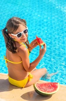 Dziewczynka dziecko zjada arbuza w pobliżu basenu