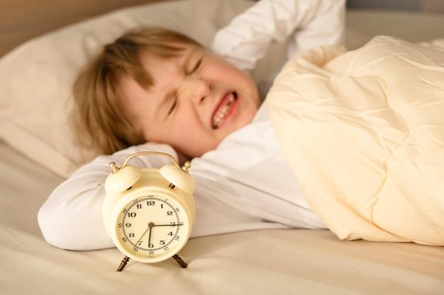 Dziewczynka, dziewczynka, zakryła uszy rękami, gdy rano dzwoni głośno budzik, odmawiając wstawania wcześnie rano