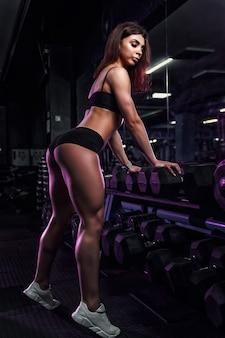 Dziewczynka fitness ćwiczenia i pozowanie ze sztangą w siłowni.