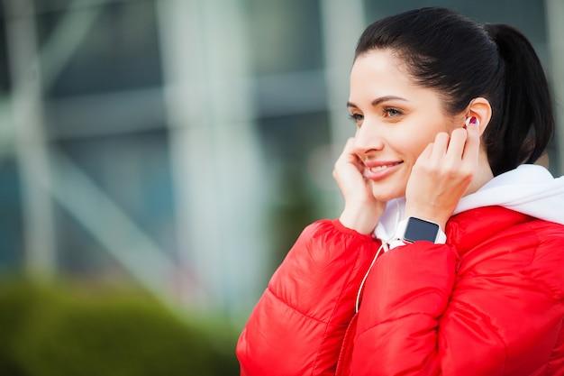 Dziewczynka fitness. dość sportowy dziewczyna działa i słuchania muzyki na świeżym powietrzu. zdrowy styl życia w dużym mieście