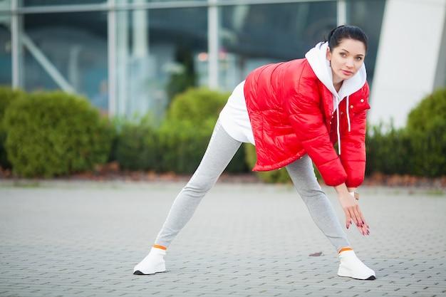 Dziewczynka fitness. młoda kobieta sportowy rozciąganie w nowoczesnym mieście. zdrowy styl życia w dużym mieście