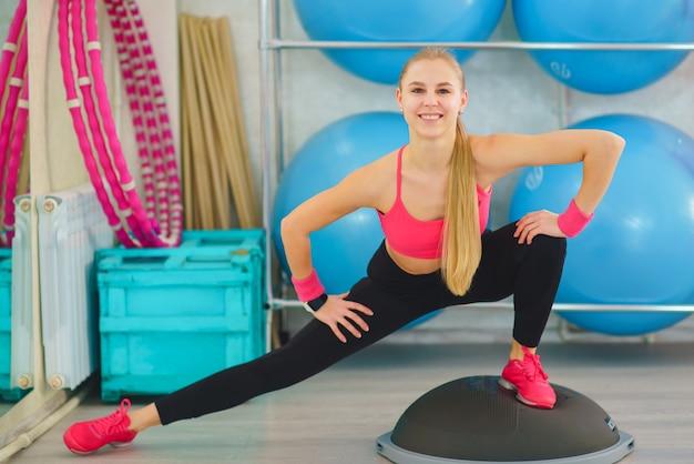 Dziewczynka fitness robi ćwiczenia z półkulą