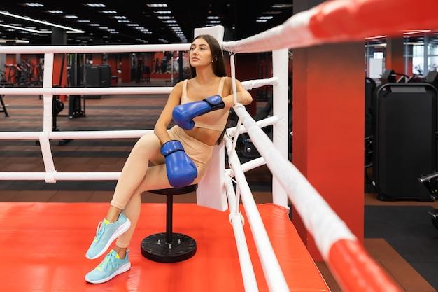 Dziewczynka fitness siedzi na ringu bokserskim