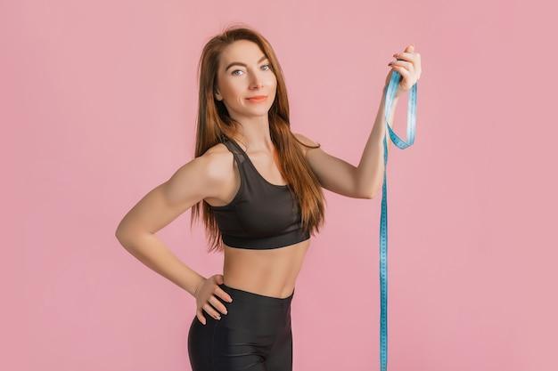 Dziewczynka fitness, uśmiechając się i pozowanie, trzymać miarkę w czarnej odzieży sportowej na różowej ścianie