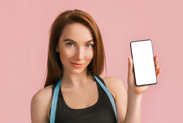 Dziewczynka fitness, uśmiechając się i trzymając telefon z makietą i pozowanie trzymać taśmę mierniczą w czarnej odzieży sportowej na różowej przestrzeni