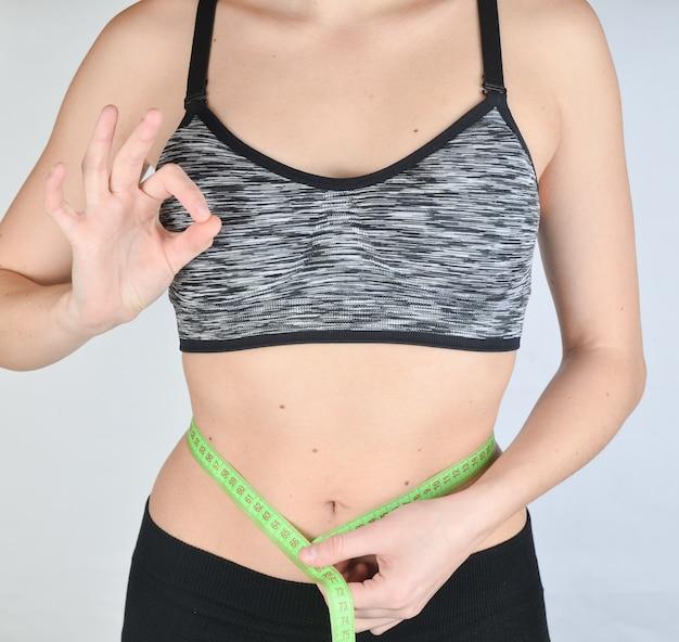 Dziewczynka fitness w sportowe topy pomiaru talii władcy. pojęcie utraty wagi.