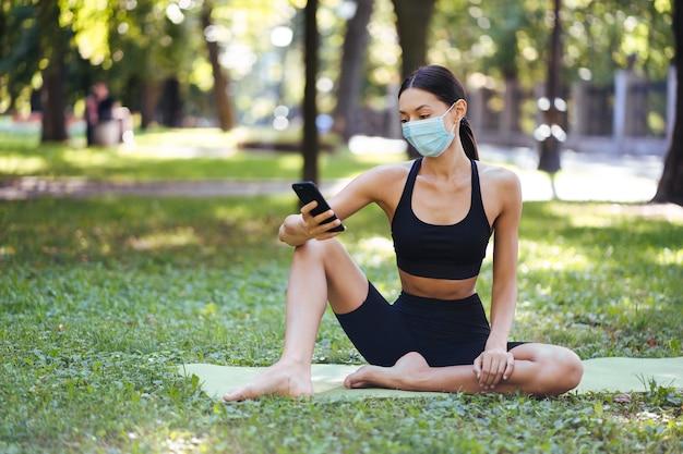 Dziewczynka fitness z smartphone na tle przyrody, lubi trening sportowy. kobieta za pomocą telefonu komórkowego na zewnątrz.