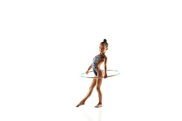Dziewczynka gimnastyczka na białym tle na białej ścianie studio.