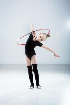 Dziewczynka gimnastyczka w czarnej sukience z hula-hoopem w studio szarym tle