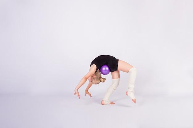 Dziewczynka gimnastyczka w czarnym stroju kąpielowym wykonuje ćwiczenie mostu z piłką na białej ścianie na białym tle z miejscem na tekst
