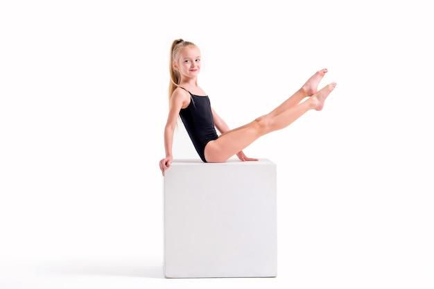 Dziewczynka gimnastyczka w czarnym stroju kąpielowym wykonuje ćwiczenie na białym sześcianie, na białym tle na białym tle