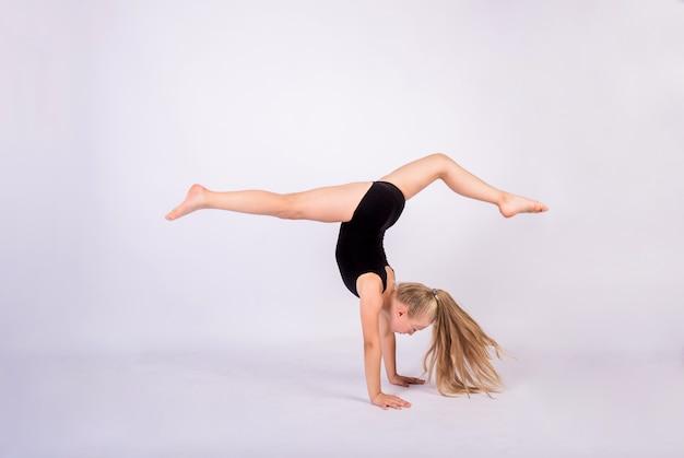 Dziewczynka gimnastyczka w czarnym stroju kąpielowym wykonuje handstand na białej ścianie na białym tle