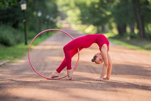 Dziewczynka gimnastyczka w czerwonym komandosie ćwiczy z obręczą w parku w letni wieczór
