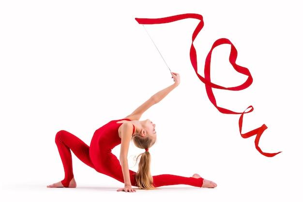 Dziewczynka gimnastyczka w czerwonym kombinezonie ćwiczy ze wstążką na białym tle, wstążka zwinięta w serce, izoluje