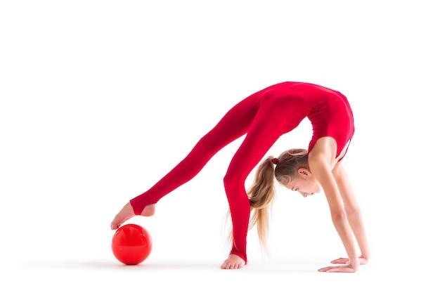 Dziewczynka gimnastyczka w czerwonym kombinezonie wykonuje ćwiczenia z piłką na białym tle