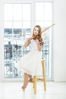 Dziewczynka gra na skrzypcach, aby uczyć się piękna i szczęśliwa w białym pokoju z dużym oknem