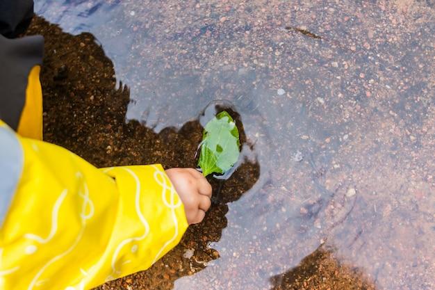 Dziewczynka gra z liści w kałuży. szczęśliwe dziecko dziewczynka gra z liści jesienią w kałuży po deszczu.