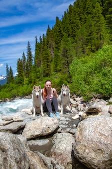 Dziewczynka gra z psami husky na brzegu rzeki górskiej