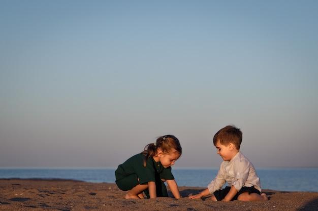 Dziewczynka i chłopiec w wieku 3-4 lat bawią się piaskiem na plaży w świetle zachodzącego słońca. skopiuj miejsce.