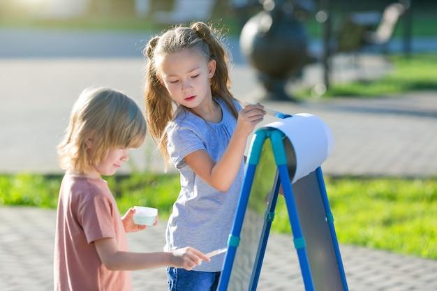 Dziewczynka i chłopiec w wieku przedszkolnym farbą pędzlem na papierze whatman na ulicy